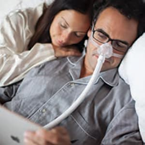 A non-intrusive nasal sleep apnea mask allowing a patient to work on a mobile device